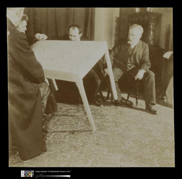 Scéance avec le medium Eusapia Palladino, vers 1907-1908: les hommes sont assis autour d'une table qui se soulève (du fait des esprits?)